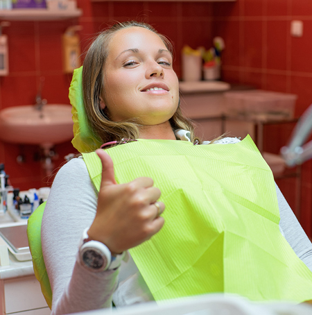 girl giving thumbs up after dental emergency